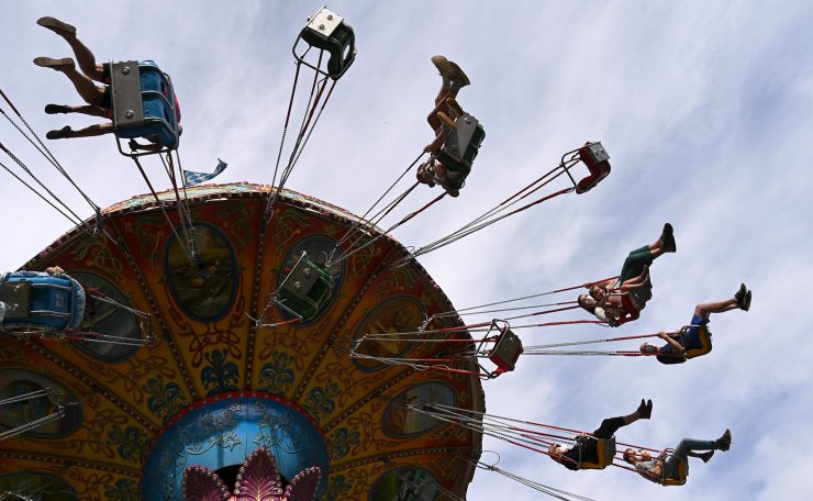 People enjoy a ride on a chairoplane at a small fairground in Munich, southern Germany, on July 3, 2021, amid the ongoing novel coronavirus (Covid-19) pandemic. - Visitors of the fair are obliged to wear face masks during their visit and on the rides. AFP