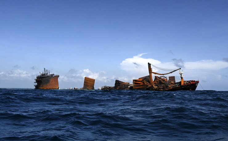 The fire stricken Singapore-registered container ship MV X-Press Pearl (L) is seen sinking while being towed away from the coast of Colombo on June 2, 2021 following Sri Lankan President Gotabaya Rajapaksa's order to move the ship to deeper water to prevent a bigger enviromental disaster. A fire broke out on a Singapore-flagged container vessel MV X-Press Pearl anchored about 9.5 nautical miles (18km) northwest of Colombo awaiting entry into the port nine days ago. The Sri Lanka Navy said an explosion caused by the chemicals being transported on the ship, including 25 tonnes of nitric acid and other chemicals loaded at the port of Hazira, India on 15 May. The 25-member crew including Philippine, Chinese, Indian and Russian nationals were evacuated by the Navy on 25 May, while two injured members were hospitalized and one was tested positive for Covid-19 on 26 May. AFP