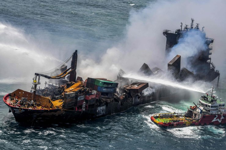 This handout photograph taken and released by the Sri Lanka Air Force on May 30, 2021 shows smoke billowing from the Singapore-registered container ship MV X-Press Pearl, which has been burning for the eleventh consecutive day as vessels try to douse off the fire, in the sea off Sri Lanka's Colombo Harbour, in Colombo. AFP