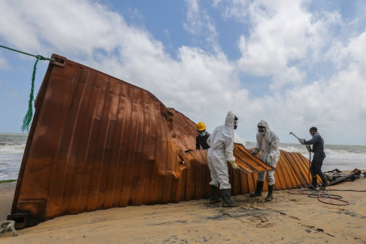 Sri Lankan Navy soldiers try to remove damaged containers on the burning cargo vessel MV X-Press Pearl, washed ashore off the coast of Colombo, Sri Lanka, 30 May 2021. EPA