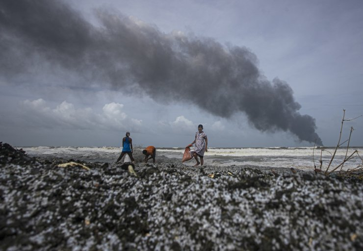 Sri Lankans salvage wreck washed off to the shore from the burning Singaporean ship MV X-Press Pearl which is anchored off Colombo port at Kapungoda, out skirts of Colombo, Sri Lanka, Wednesday, May 26, 2021. A fire on a container ship carrying chemicals raged off Sri Lanka for a sixth day Wednesday and India sent vessels to help douse the blaze, officials said. AP