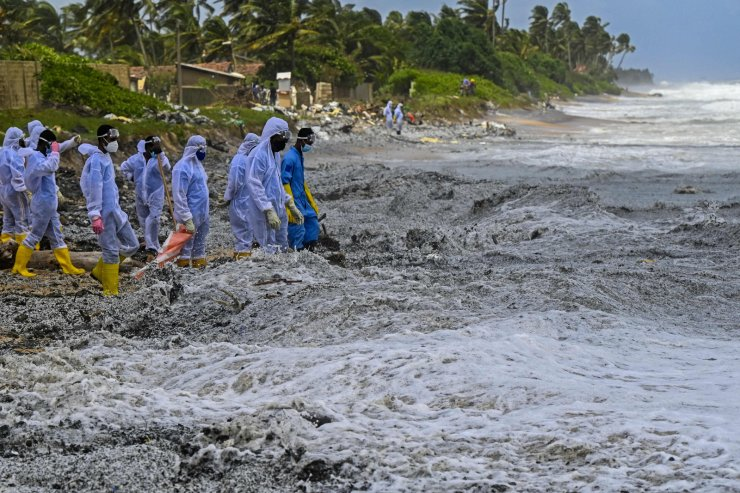 Sri Lankan Navy soldiers work to remove debris washed ashore from the Singapore-registered container ship MV X-Press Pearl, which has been burning for the eighth consecutive day in the sea off Sri Lanka's Colombo Harbour, on a beach in Colombo on May 27, 2021. AFP