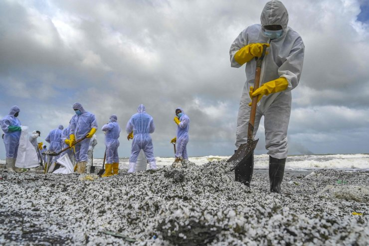 Sri Lankan Navy soldiers work to remove debris washed ashore from the Singapore-registered container ship MV X-Press Pearl, which has been burning for the ninth consecutive day in the sea off Sri Lanka's Colombo Harbour, on a beach in Colombo on May 28, 2021. AFP