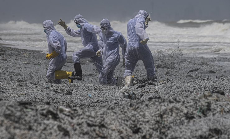 Sri Lankan navy soldiers clad in protective suits attempt to evade a wave drifting debris ashore from the burning Singaporean ship MV X-Press Pearl which is anchored off Colombo port at Kapungoda, out skirts of Colombo, Sri Lanka, Thursday, May 27, 2021. AP