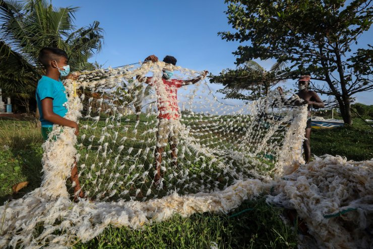 Sri Lankan fishermen hold a fishing net with plastic fiber clinging on it due to materials polluting the sea from the fire ravaged MV X-Press Pearl which is now sinking off the coast of Colombo, Sri Lanka, June, 2, 2021. EPA