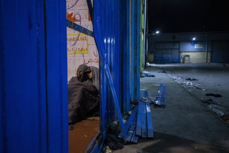 Two minors sleep inside a warehouse turned into a makeshift center for minors at the Spanish enclave of Ceuta, at the border of Morocco and Spain, late Tuesday, May 18, 2021. AP