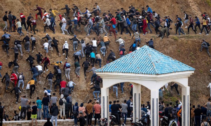 Migrants avoid the Moroccan police as they try to reach the border between Morocco and thr Spanish enclave of Ceuta on May 18, 2021 in Fnideq. AFP