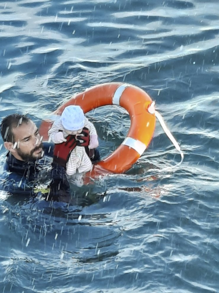 In this photo provided by the Spanish Civil Guard in Ceuta, Spain, on Tuesday May, 18, 2021, a member of the civil guard rescues a baby that was separated from its parents, who were migrants, in the sea off Ceuta, Spain. Spain's North African enclave of Ceuta is facing a humanitarian crisis after thousands of migrants swum around or jumped a border fence left unguarded by Morocco as part of a diplomatic row with its European neighbor. Guardia Civil via AP