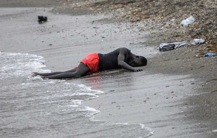 A man lies on the ground on the beach after swimming to the area at the border of Morocco and Spain, at the Spanish enclave of Ceuta, on Tuesday, May 18, 2021. AP