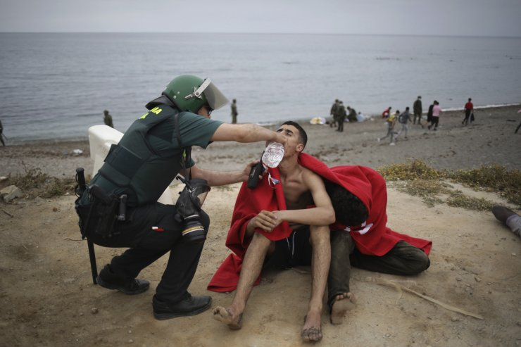 A man from Morocco is assisted by a Guardia Civil officer as he arrives swimming at the Spanish enclave of Ceuta, on Tuesday, May 18, 2021. AP