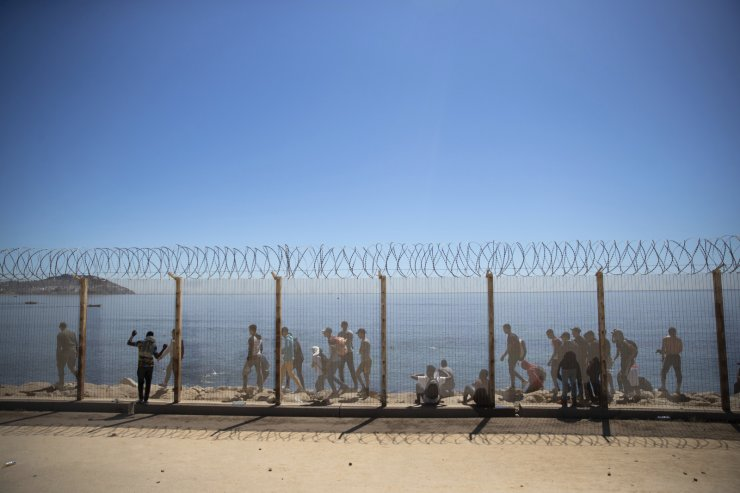 Moroccan and sub-saharan migrants walk past a fence separating the Moroccan and Spanish side of the border near the Spanish enclave of Ceuta, Wednesday, May 19, 2021. AP