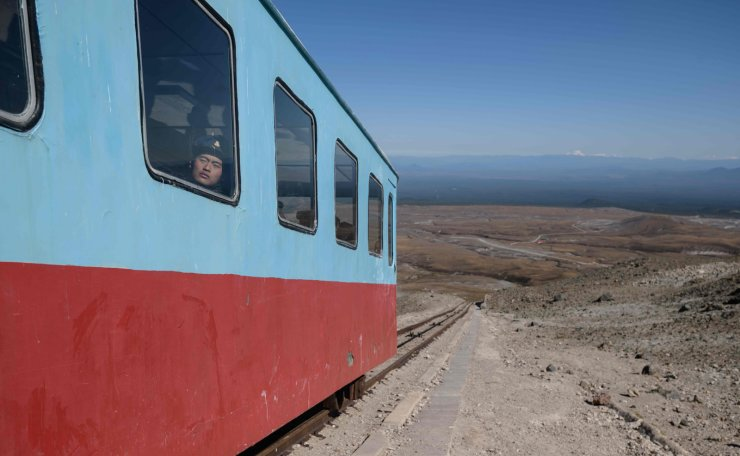In a photo taken on September 11, 2019, North Korean visitors ride a funicular railway as they descend from a viewing platform near the summit of Mount Paektu, near Samjiyon. Mount Paektu has long been considered the spiritual birthplace of the Korean nation and is a place of pilgrimage for tens of thousands of North Koreans every year, who are trained from birth to revere their leaders. Every year 100,000 North Koreans or more are taken on study tours to the camp, the mountain, and nearby revolutionary sites where relics of operations are preserved. Dressing in khaki uniforms said to resemble guerrillas' outfits and carrying red flags, they march to the summit of the volcano. AFP