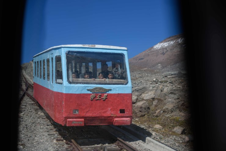 In a photo taken on September 11, 2019, a group of North Korean visitors ride a funicular railway as they descend from a viewing platform at Mount Paektu, near Samjiyon. AFP