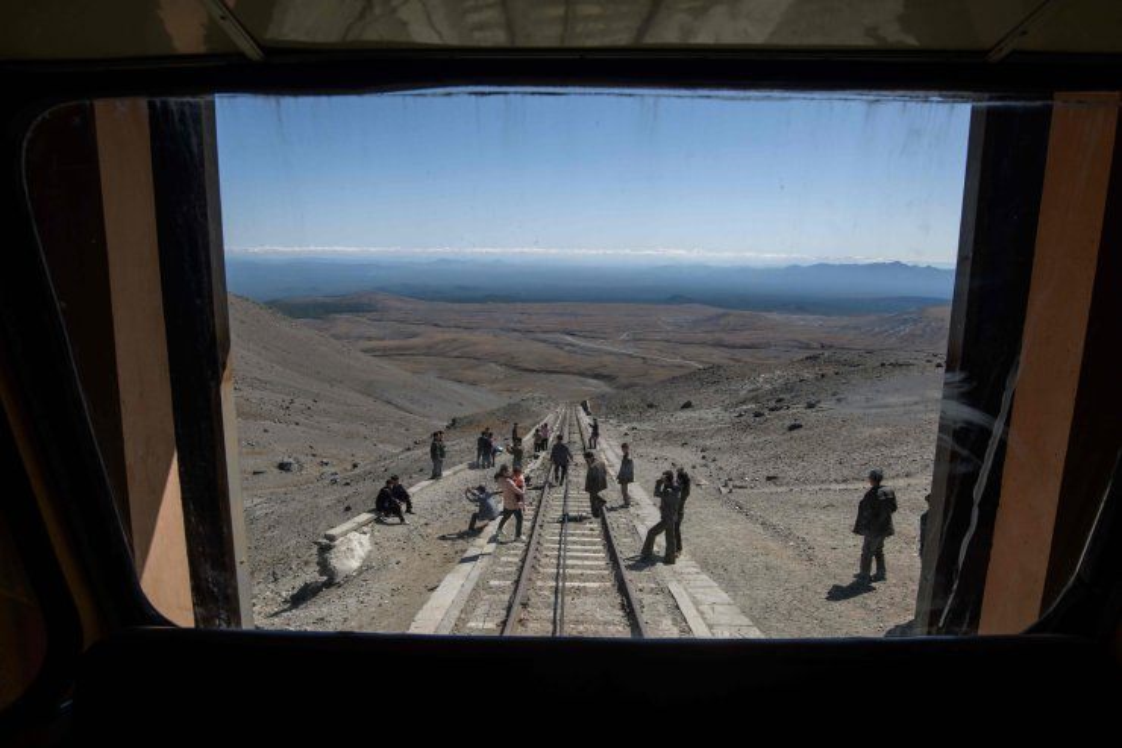 In a photo taken on September 11, 2019, North Korean visitors take photos after riding a funicular railway to a viewing platform near the summit of Mount Paektu, near Samjiyon. AFP