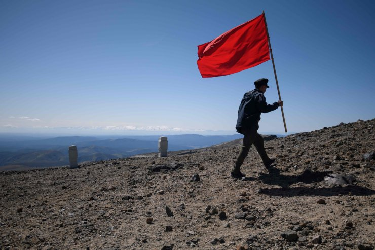 In a photo taken on September 11, 2019, a North Korean student carries a flag during a march to the summit of Mount Paektu, near Samjiyon. AFP