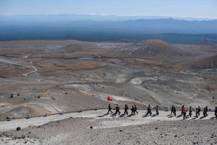 In a photo taken on September 11, 2019, a group of North Korean students march as they visit Mount Paektu, near Samjiyon. AFP