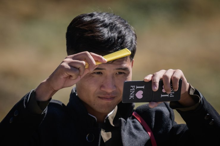 In a photo taken on September 11, 2019, a North Korean student brushes his hair after paddling in Chonji lake, or 'Heaven lake', in the crater of Mount Paektu, near Samjiyon. AFP