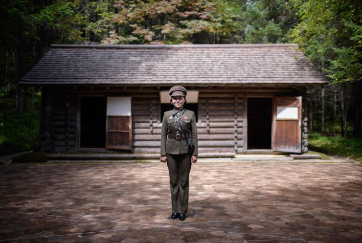 A photo taken on September 12, 2019, shows guide Kim Un-sim(23) posing for a portrait before a replica of a cabin said to be used by Kim Il-sung at the 'Secret Camp, said to be the birthplace of late North Korean leader Kim Jong-il, near Samjiyon. AFP