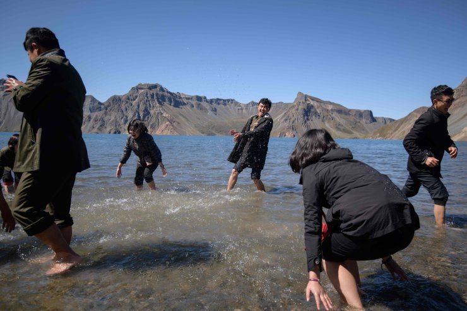 In a photo taken on September 11, 2019, North Korean students play in Chonji lake, or 'Heaven lake', as they visit the crater of Mount Paektu, near Samjiyon. AFP
