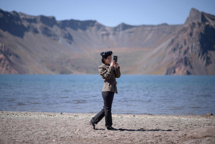 In a photo taken on September 11, 2019, a North Korean student holds a mobile phone as she stands before Chonji lake, or 'Heaven lake', in the crater of Mount Paektu, near Samjiyon. AFP