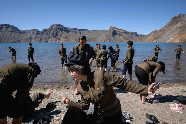 In a photo taken on September 11, 2019, North Korean students stand in Chonji lake, or 'Heaven lake', as they visit the crater of Mount Paektu, near Samjiyon. AFP