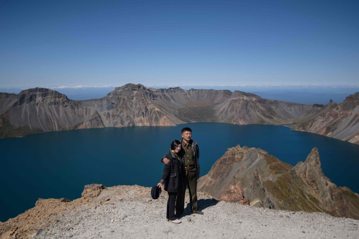 In a photo taken on September 11, 2019, North Korean students pose for photos as they march to the summit of Mount Paektu, near Samjiyon. AFP