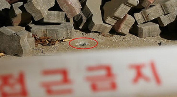 Pictured is a hole left in the ground by North Korean machine-gun fire in the border county of Yeoncheon, Gyeonggi Province. / Yonhap