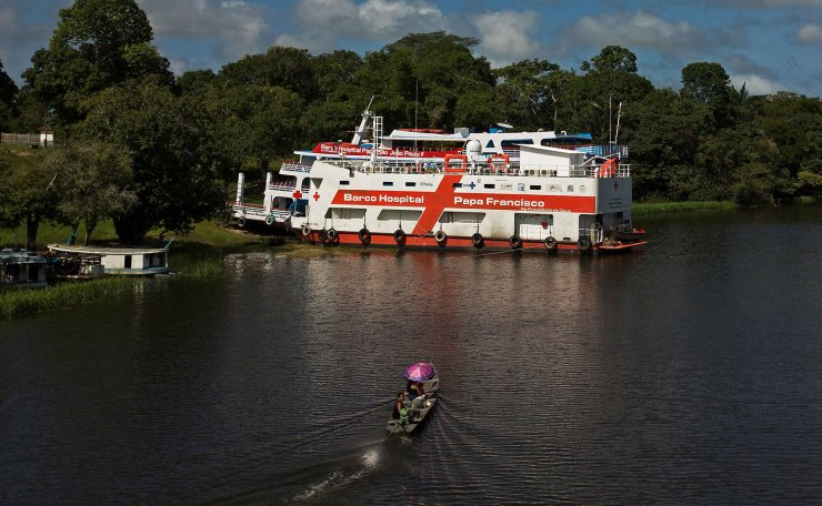 A patient on a canoe approaches the Papa Francisco boat hospital moored on a river on the border between Para and Amazonas states, in Brazil, on February 5, 2021. - Two hospital boats, the Papa Francisco and Sao Joao Paulo ll, perform various COVID-19 related services. There are more than 15 health professionals in action onboard at any time. It is a health project with Vatican support and funding from the state of Para. AFP