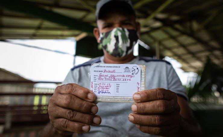 Rosane Nascimento, 44, a member of the Mura ethnia, shows the register of his vaccine, at the Aldeia Sao Felix, Autazes municipality, Amazonas state, Brazil, 05 February 2021 (Issued 06 February 2021). Health workers are facing severe challenges in vaccinating indigenous people in Brazil, where spreading has increased, and a new variant of the coronavirus has been discovered.  EPA