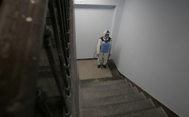 A volunteer waits on the staircase to start disinfection at Pirogov hospital in Sofia, Sunday, Feb. 7, 2021. Bulgarians on Sunday received their first doses of the AstraZeneca COVID-19 vaccine as the country is struggling to increase the number of inoculations to catch up with the other EU member nations. AP
