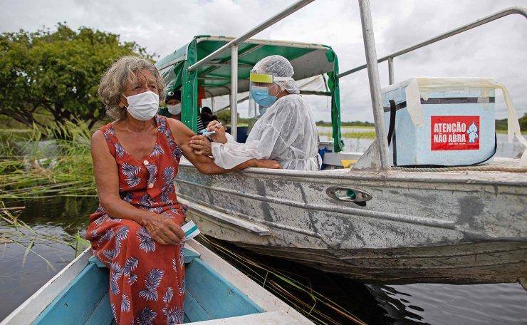 Olga D'arc Pimentel, 72, is vaccinated by a health worker with a dose of AstraZeneca's COVID-19 vaccine in the Nossa Senhora Livramento community on the banks of the Rio Negro near Manaus, Amazonas state, Brazil on February 9, 2021. AFP