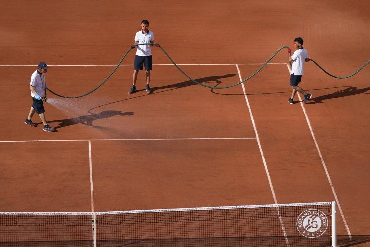 Employees water a court during the first round match of the French Open tennis tournament at the Roland Garros stadium Sunday, May 30, 2021 in Paris. AP