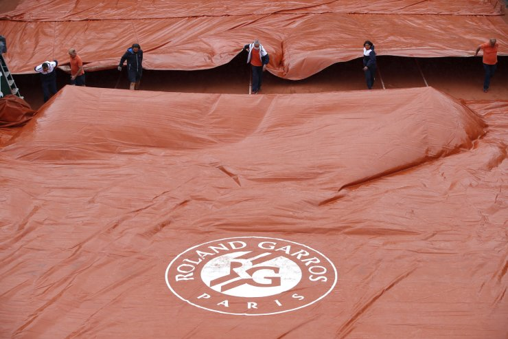 Covers are pulled over the court as rain stops play at Roland Garros in Paris, France, June 4. REUTERS