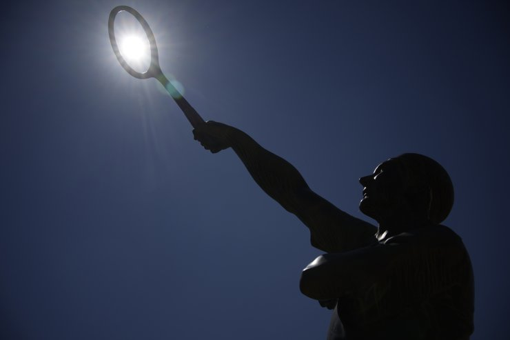 The sun shines behind the statue of Jean Laurent Robert Borotra a former French Open champion on day two of the French Open tennis tournament at Roland Garros in Paris, France, Monday, May 31, 2021. AP