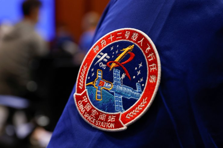 A badge of the Shenzhou-12 Manned Space Flight Mission is seen on the uniform of a staff member of the Jiuquan Satellite Launch Center during a news conference before the Shenzhou-12 mission to build China's space station, at Jiuquan Satellite Launch Center in Gansu province, China June 16, 2021. REUTERS