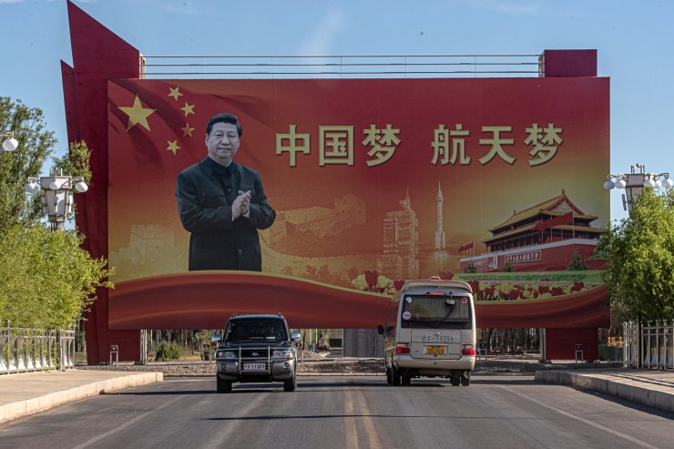 Vehicles drive past a banner showing Chinese President Xi Jinping at the Jiuquan Satellite Launch Center, the day before the launching of Long March-2F carrier rocket, carrying the Shenzhou-12, in China's northwestern Gansu province, 16 June 2021. China will launch Shenzhou-12 spacecraft carrying three crew members to the orbiting Tianhe core module for a three-month mission on 17 June. It is the first spaceflight in almost five years when China sends humans into space. EPA