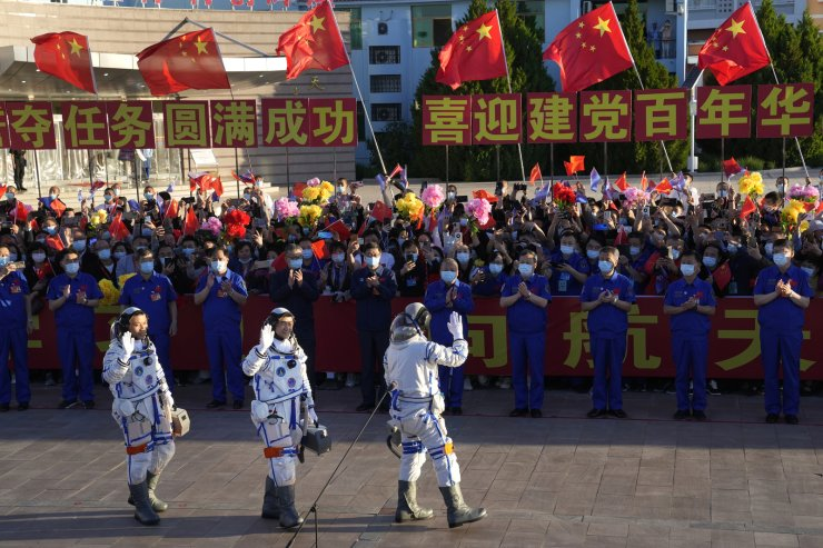 Chinese astronauts, from left, Tang Hongbo, Liu Boming, and Nie Haisheng wave as they prepare to board for liftoff at the Jiuquan Satellite Launch Center in Jiuquan in northwestern China, Thursday, June 17, 2021. China plans on Thursday to launch three astronauts onboard the Shenzhou-12 spaceship who will be the first crew members to live on China's new orbiting space station Tianhe, or Heavenly Harmony. AP