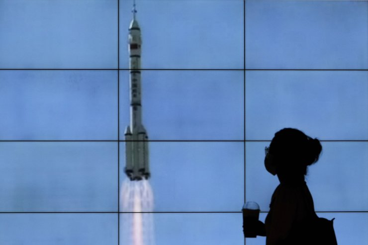A woman wearing a face mask is silhouetted as she walks by a TV screen showing CCTV live telecast of the Long March-2F Y12 rocket carrying a crew of Chinese astronauts in a Shenzhou-12 spaceship lifts off at the Jiuquan Satellite Launch Center, at a shopping mall in Beijing, Thursday, June 17, 2021. China launched the first three crew members on a mission to its new space station Thursday in its first crewed mission in five years. AP