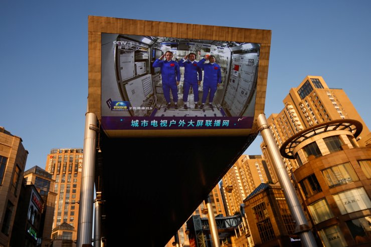 A giant screen shows Chinese astronauts Nie Haisheng (C), Liu Boming (R), and Tang Hongbo of the Shenzhou-12 mission saluting inside the Tianhe core module of China's space station, at a shopping mall in Beijing, China June 18, 2021. REUTERS