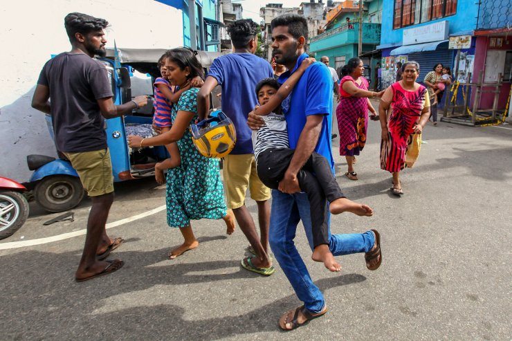 Sri Lankans living near St. Anthony's shrine run for safety after police found explosive devices in parked vehicle, which later exploded in Colombo, Sri Lanka, Monday, April 22, 2019. Easter Sunday bombings that ripped through Sri Lanka's churches and luxury hotels killed more than 200 people. AP