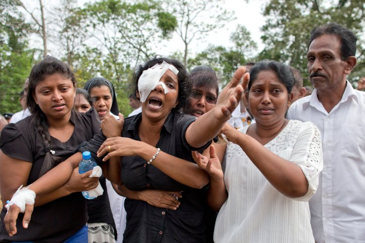 Anusha Kumari, second from left, weeps during a mass burial for her husband, two children and three siblings, all victims of Easter Sunday's bomb attacks, in Negombo, Sri Lanka, Wednesday, April 24, 2019. In an instant on Easter Sunday, Kumari, 43, was left childless and a widow when suicide bombers launched a coordinated attack on churches and luxury hotels in and just outside Sri Lanka's capital, Colombo. AP