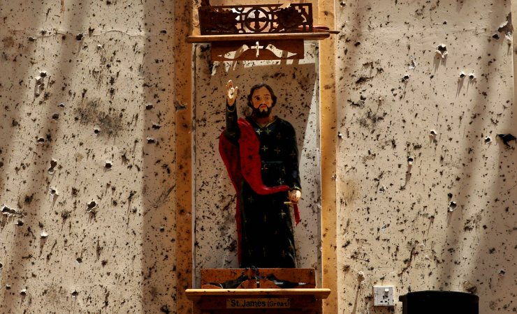 A statue of St. James stands on a wall speckled with fragments of shrapnel at St. Sebastian's Church, where a suicide bomber blew himself up in Negombo, north of Colombo, Sri Lanka, Thursday, April 25, 2019. AP