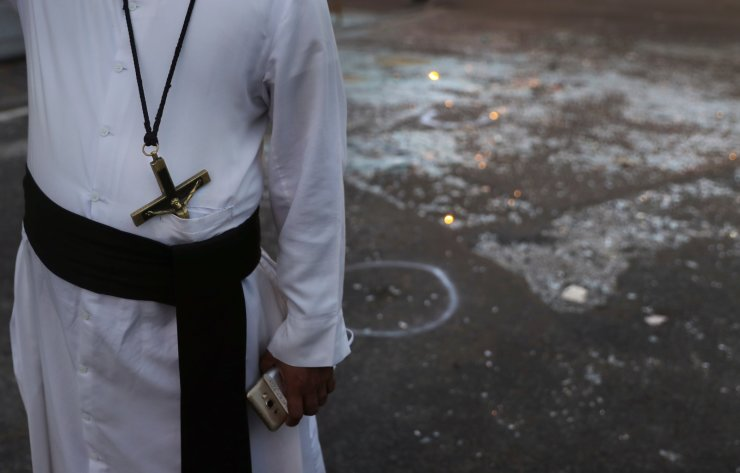 A Sri Lankan catholic priest stands near broken glass in front St. Anthony's Church in Colombo, Sri Lanka, Friday, April 26, 2019. Priests have allowed journalists inside St. Anthony's Church in Sri Lanka for the first time since it was targeted in a series of Islamic State-claimed suicide bombings that killed over 250 people. Broken glass littered the sanctuary's damaged pews and blood stained the floor. Shoes left by panicked worshippers remained in the darkened church, and broken bottles of holy water lay on the floor. AP