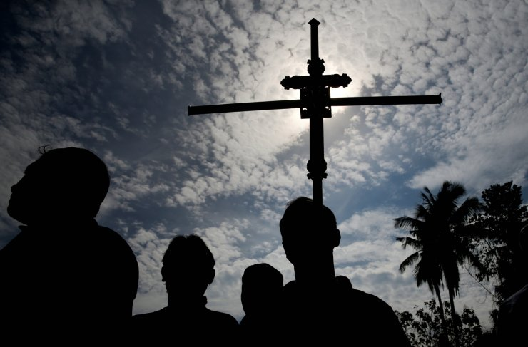 A man holds a cross during a mass burial of victims, two days after a string of suicide bomb attacks on churches and luxury hotels across the island on Easter Sunday, at a cemetery near St. Sebastian Church in Negombo, Sri Lanka April 23, 2019. Reuters