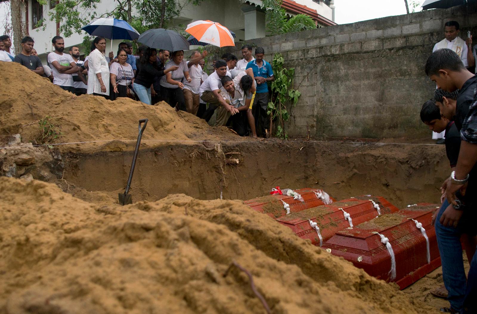 Relatives bury three members of the same family, all died at Easter Sunday bomb blast at St. Sebastian Church in Negombo, Sri Lanka, Monday, April 22, 2019. AP