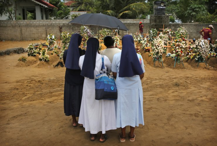 Catholic nuns stand with a relative of a victim of Easter Sunday's bomb blast at St. Sebastian Church at a mass burial site in Negombo, Sri Lanka Thursday, April 25, 2019. The U.S. Embassy in Sri Lanka warned Thursday that places of worship could be targeted for militant attacks over the coming weekend, as police searched for more suspects in the Islamic State-claimed Easter suicide bombings that killed over 250 people. AP