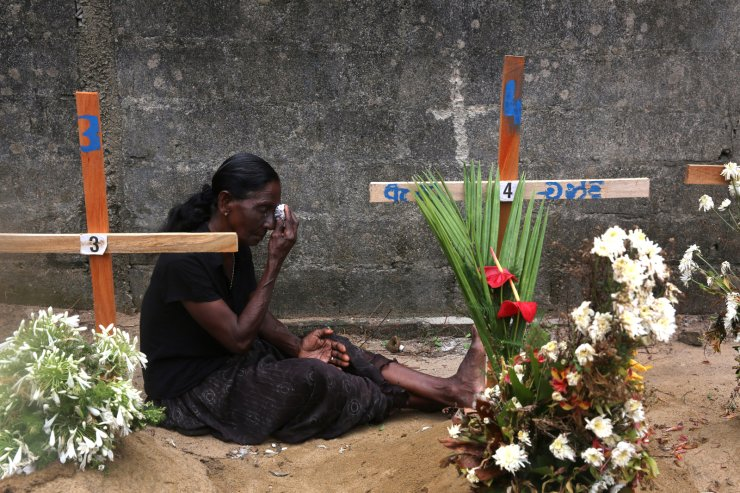 A relative of a victim of Easter bomb blasts wipes her tears during a prayer at the burial site of her relatives after a televised Sunday mass by Sri Lankan Archbishop Cardinal Malcolm Ranjith, in Negombo, north of Colombo, Sri Lanka, Sunday, April 28, 2019. Sri Lanka's Catholics celebrated Sunday Mass in their homes by a televised broadcast as churches across the island nation shut over fears of militant attacks, a week after the Islamic State-claimed Easter suicide bombings killed over 250 people. AP