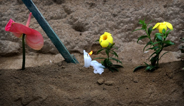 A candle and fresh flowers are placed on the cemetery of a victim of Easter bomb blast, in Negombo, north of Colombo, Sri Lanka, Sunday, April 28, 2019. AP