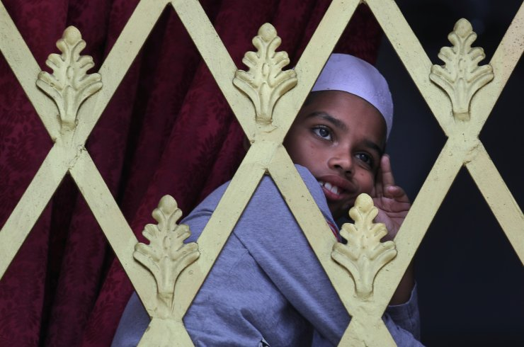 A Sri Lankan Muslim boy looks out from the window of a Mosque before the Friday prayers in Colombo, Sri Lanka, Friday, April 26, 2019. Across Colombo, there was a visible increase of security as authorities warned of another attack and pursued suspects that could have access to explosives. Authorities had told Muslims to pray at home rather than attend communal Friday prayers that are the most important religious service for the faithful. At one mosque in Colombo where prayers were still held, police armed with Kalashnikov assault rifles stood guard outside. AP