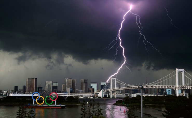 A lightning looks over the statue of the Olympics rings installed near a park being prepared for the Olympic and Paralympic Games in Tokyo, Sunday, July 11, 2021. The opening ceremony of the postponed 2020 Summer Olympics is scheduled to be held in less than two weeks. AP